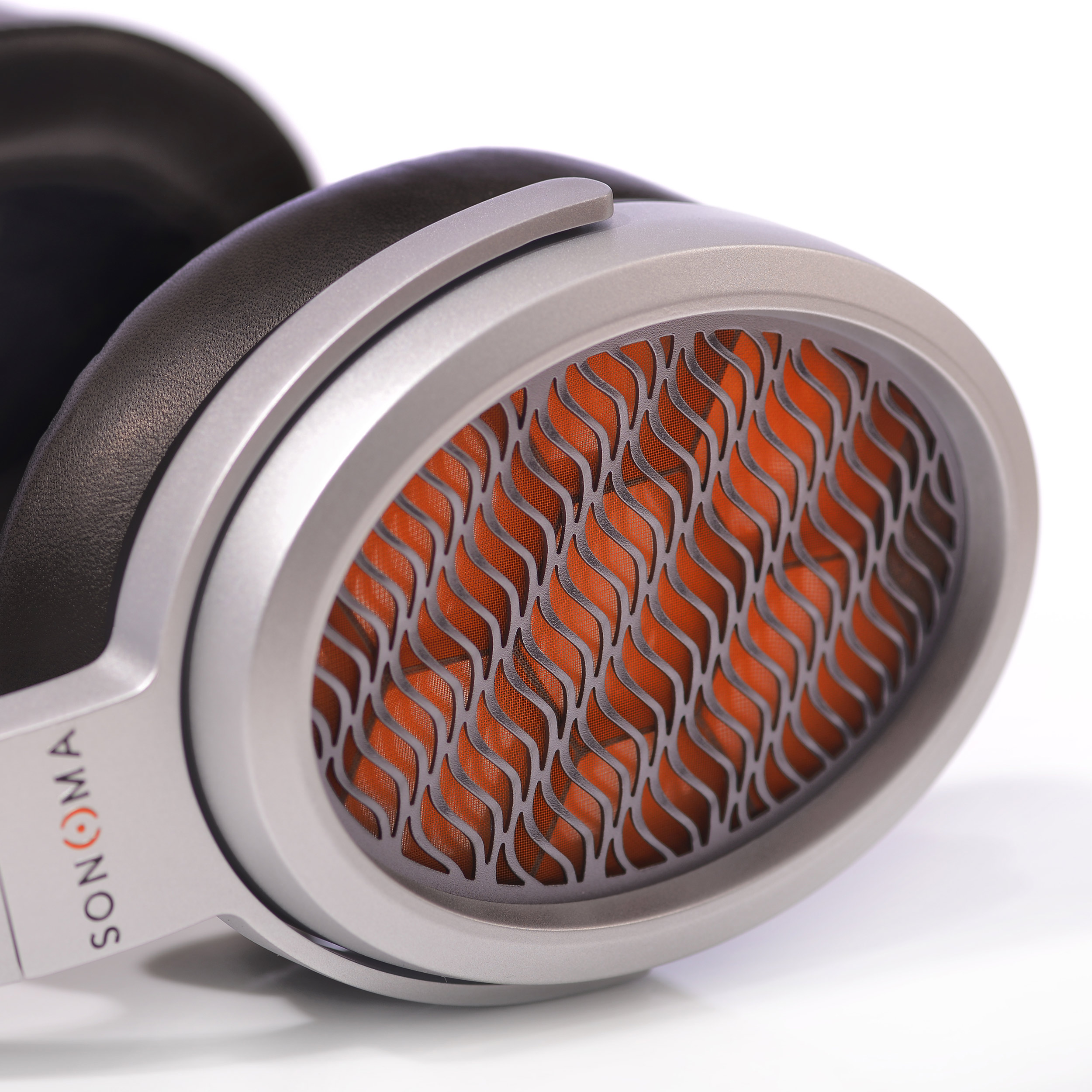 Oval shaped, injected magnesium silver earcups with orange honeycomb HPEL visible through a wavy metal mesh