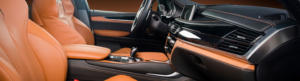 Front interior view of a luxury car with tan leather seats and dashboard accents