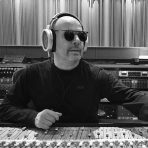 A man wearing sunglasses and a dark long sleeved t-shirt using the Sonoma Headphones to mix music